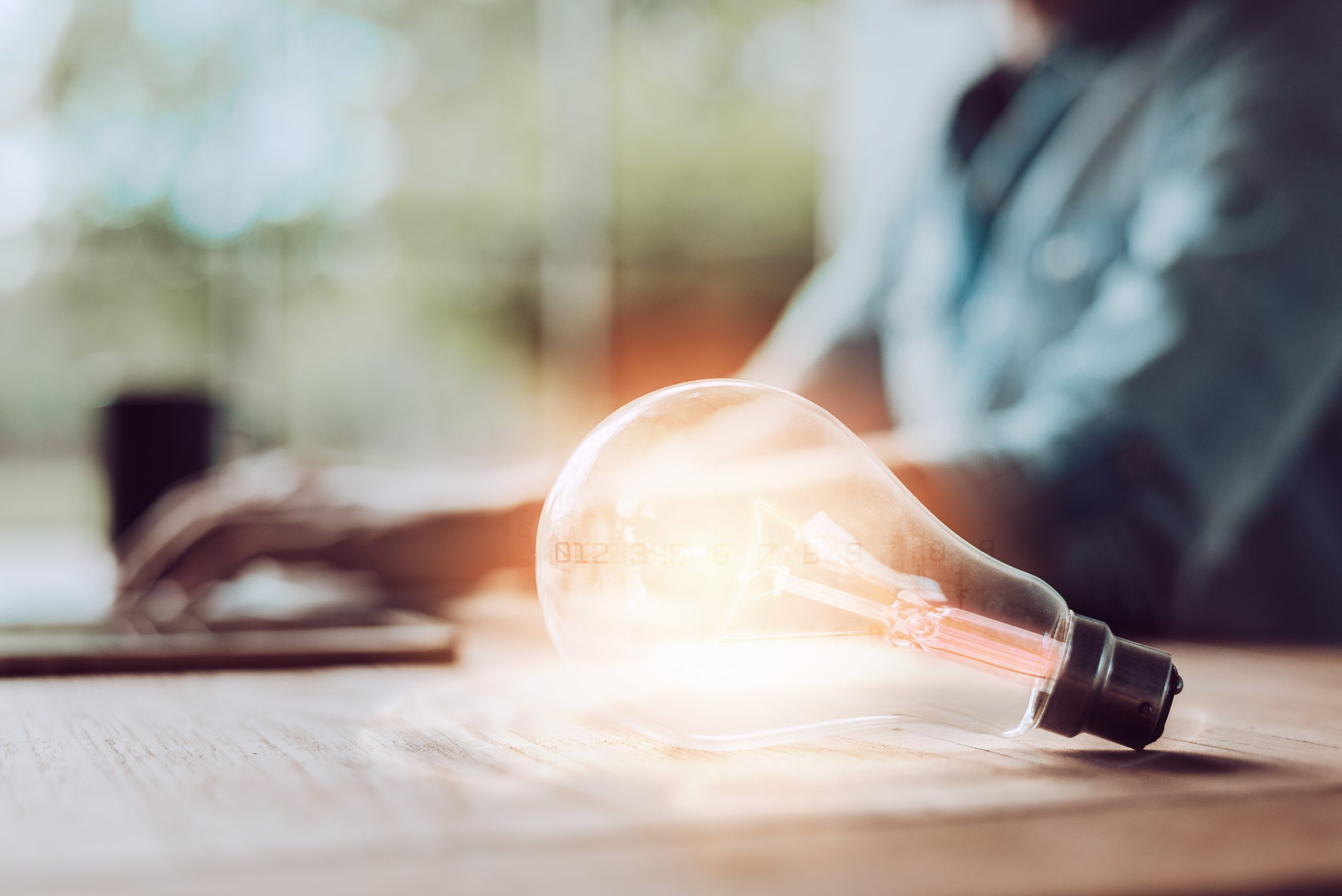 lightbulb on table in front on man on computer