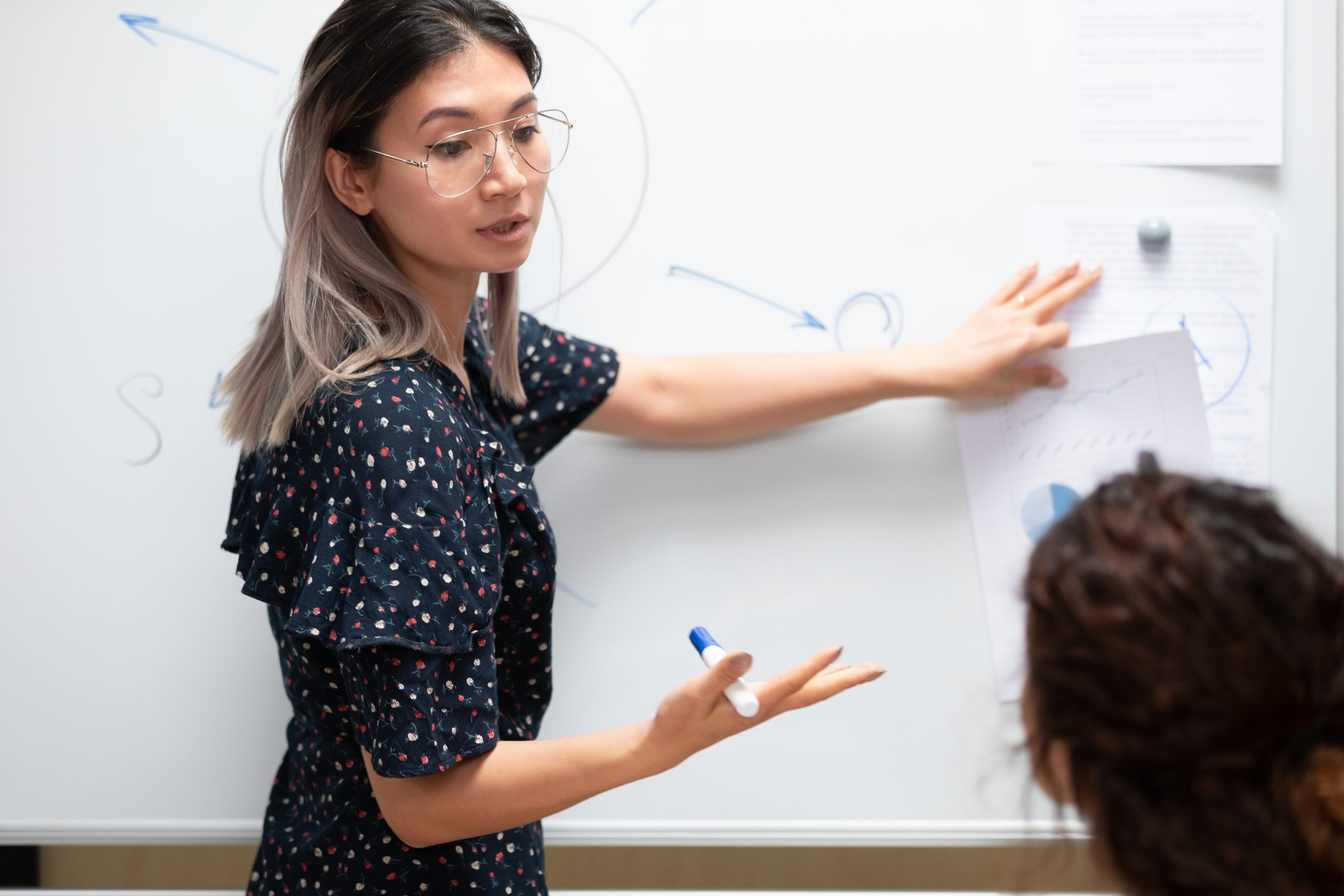 woman teaching other on white board