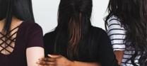 Three girls holding onto eachother image